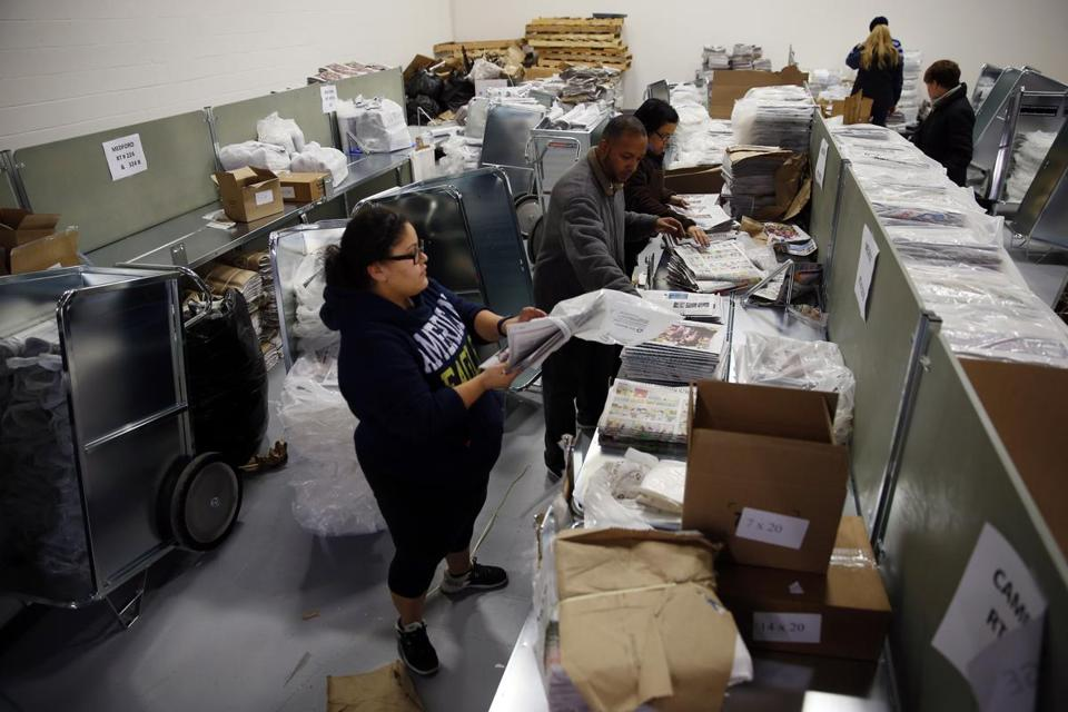 Workers bundled papers inside a distribution center in Woburn before they delivered the Sunday Boston Globe.