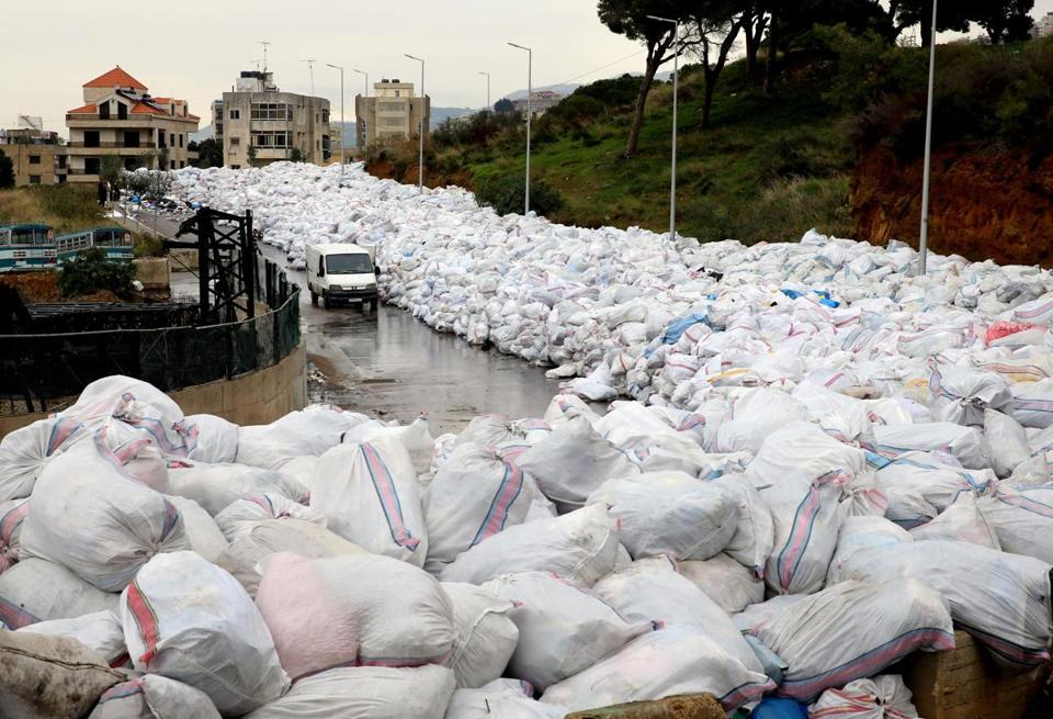 A van drove past piles of wrapped garbage blocking a road in the town of Jdeideh, northeast of Beirut, on Monday.