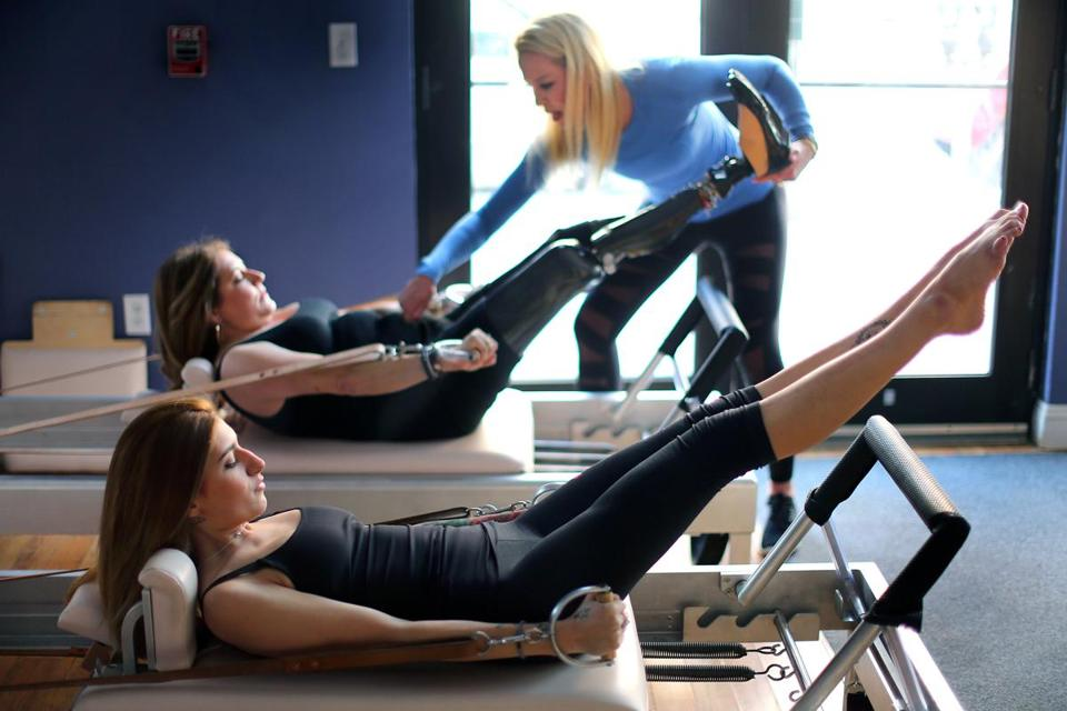 Marathon bombing survivors Sydney Corcoran (foreground) and her mother, Celeste, do pilates under the supervision of instructor Julie Erickson at the Endurance Pilates and Yoga Studio.