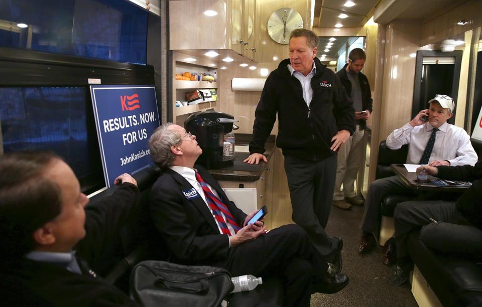With Ohio attorney general Mike Dewine (second from left) aboard, John Kasich headed for another New Hampshire stop on his campaign bus Tuesday.