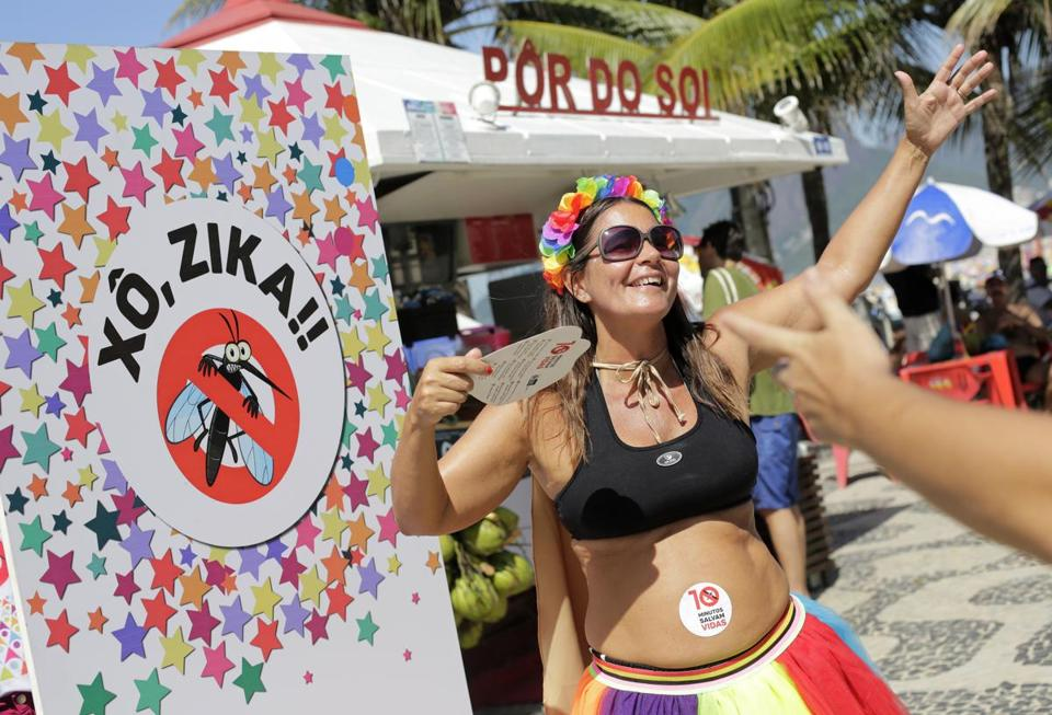 "A pregnant woman danced near a sign that says ""Get out Zika"" during a carnival in Rio de Janeiro. Health officials were distributing Zika-prevention advice on the streets Sunday."