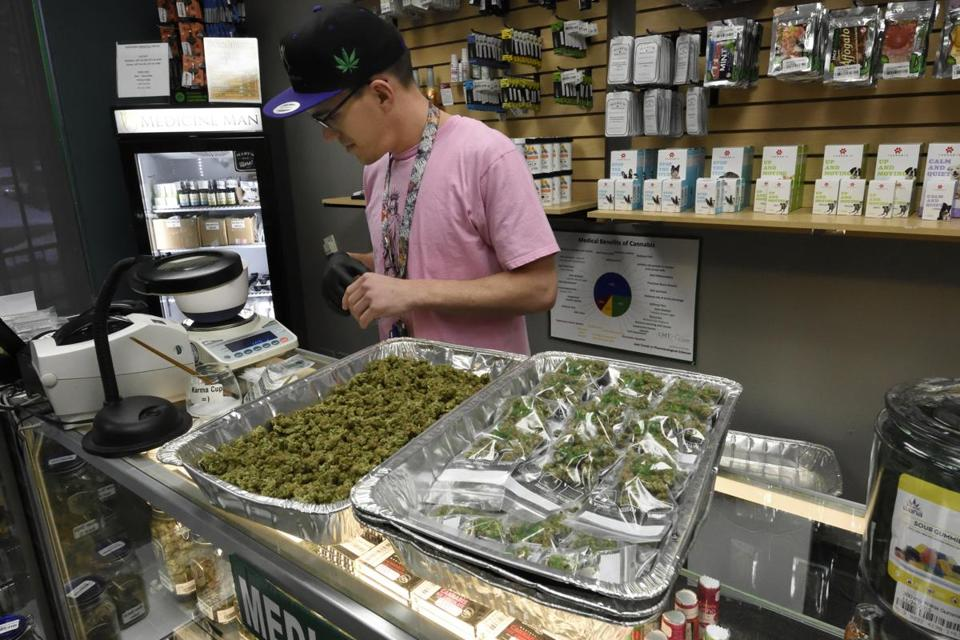 Matthew Benton weighs and packages marijuana buds for sale at their retail counters at the Medicine Man marijuana dispensary in Denver.