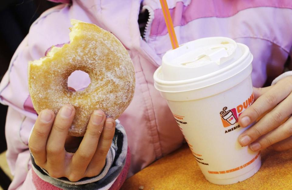 FILE - In this Thursday, Feb. 14, 2013, file photo, a girl has a doughnut and a beverage at a Dunkin' Donuts in New York. Dunkin' Brands reports financial earnings on Thursday, Feb. 4, 2016. (AP Photo/Mark Lennihan, File)