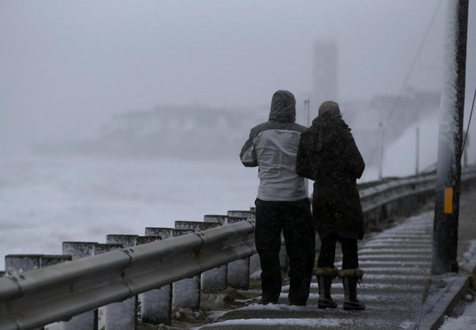 A couple takes in the view from the Brant Rock Seawall in Marshfield February 2016. (Craig F. Walker/Globe Staff)