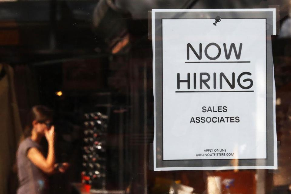 "A ""Now Hiring"" sign hangs on the door to the Urban Outfitters store at Quincy Market in Boston, Massachusetts in this September 5, 2014 file photo. The number of Americans filing for unemployment benefits fell more than expected last week, suggesting the labor market remains on solid footing despite slowing economic growth and a stock market rout. REUTERS/Brian Snyder/Files"