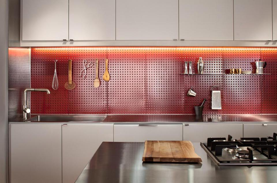 Outfitted with pegboard accessories from the local hardware store, the aligator board in this kitchen serves as custom storage for kitchen utensils and other small gadgets.