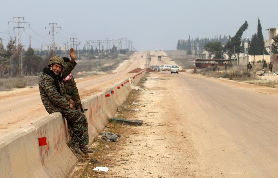 A member of the Syrian government forces waved as he sat on the road leading to Gaziantep on the outskirts of the village of Kiffin on Thursday.