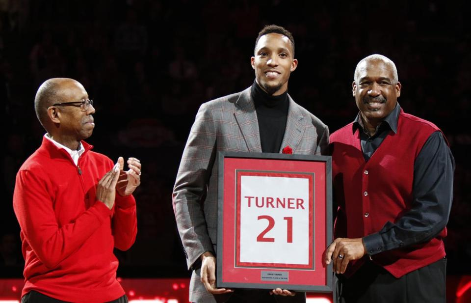 Former Ohio State basketball player and current member of the Boston Celtics Evan Turner, center, is presented with a replica of his college jersey by Ohio State University president Dr. Michael Drake, left, and athletic director Gene Smith after having his college jersey number hung from the rafters during a ceremony at half-time of an NCAA college basketball game between Ohio State and Michigan in Columbus, Ohio, Tuesday, Feb. 16, 2016. (AP Photo/Paul Vernon)
