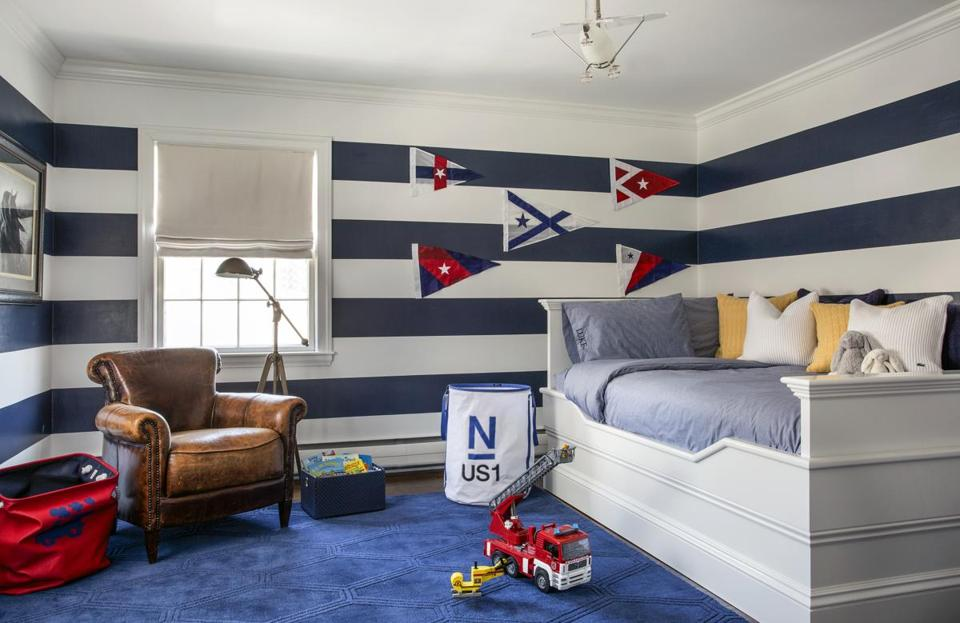 The blue and white striped walls are the most notable feature of the nautical-themed boy's room.