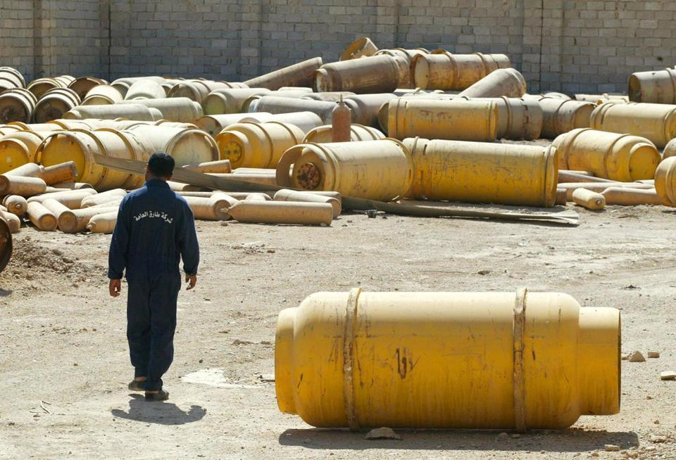 "The security chief of Fallujah II chlorine plant, Mohammed Abid, walks among chlorine canisters in the plant's yard in Mulahimah, Iraq Thursday Oct. 2, 2003. Once the CIA's ""best example"" of a disguised weapons program, the derelict chemical plant stands today more as a symbol of the gap between fears and reality in the Iraqi crisis. (AP Photo/Greg Baker)"