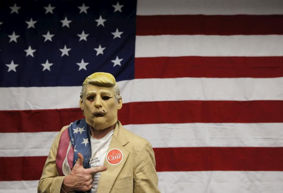 Michael Harwood, a supporter of GOP presidential candidate Ted Cruz, wears a Donald Trump mask.