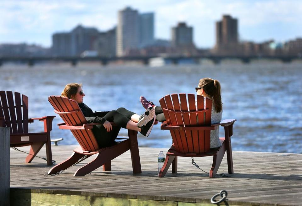 Suffolk University students Brenna McCoubrey (left) and Gina Gates lounged on a dock on the Charles River Esplanade after their classes.