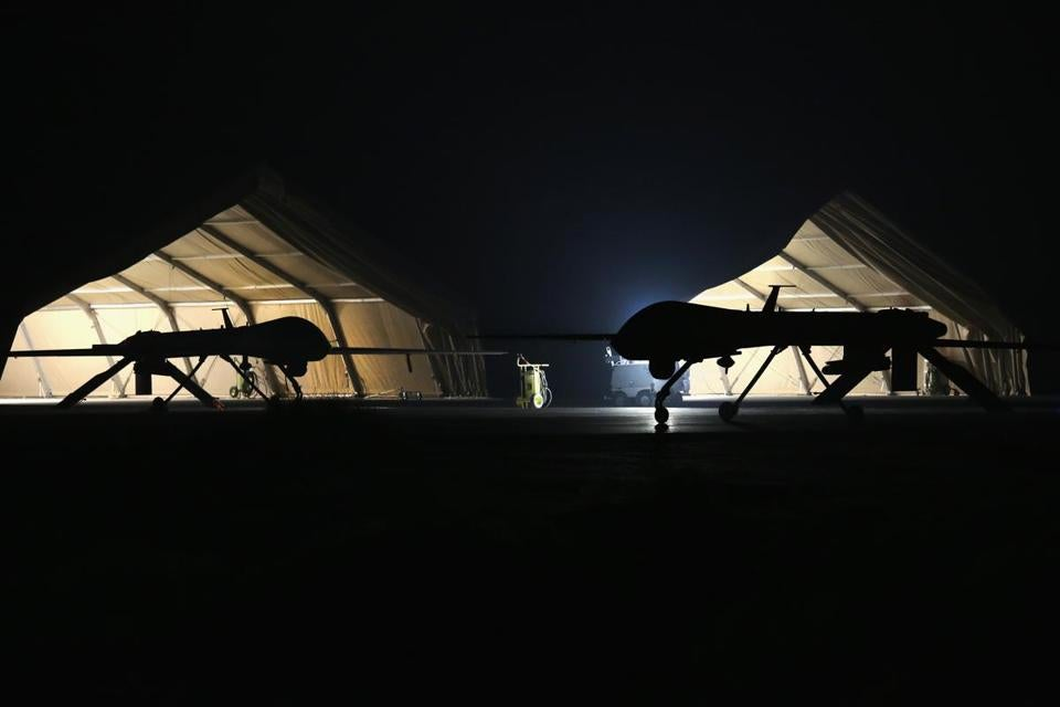 A U.S. Air Force MQ-1B Predator unmanned aerial vehicle (UAV), (R), returns from a mission to an air base in the Persian Gulf region on January 7, 2016.