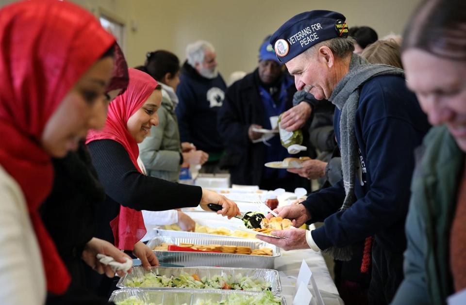 Gilane Shaker, left, of the Islamic Society of Boston Cultural Center served food to US Navy veteran David Bonner during a gathering in Boston on Saturday.