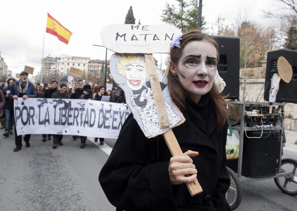 A woman holds a banner picturing a puppeteer and reading 'They kill me' during a rally in support of two Spanish puppeters, accused of glorifying terrorism, in Granada, southern Spain, Feb. 13.