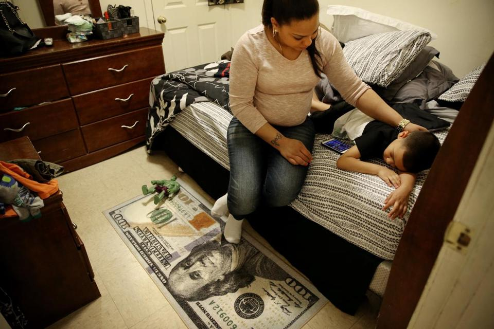 Lany Ruiz comforted her son, Alex, 5, in her bedroom at their home in the lower South End of Boston.