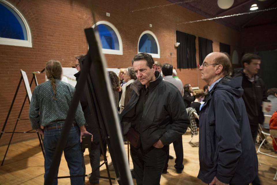"3/2/2016 - Somerville, MA - Irving Fischman, cq, center, of Somerville, looked at plans for scaled-back plans for the MBTA Green Line extension project during a community forum at the Somerville Armory on Wednesday evening, March 2, 2016. ""They cut it back way too much,"" said Fischman. ""There's no protection [from the elements], and last year's winter was terrible. The handicap access is really horrible,"" added Fischman. The room was standing-room only, and there was a line out the door of people waiting to get in the building. Story by Nicole Dunga/Globe Staff. Topic: 03greenline. Photo by Dina Rudick/Globe Staff."