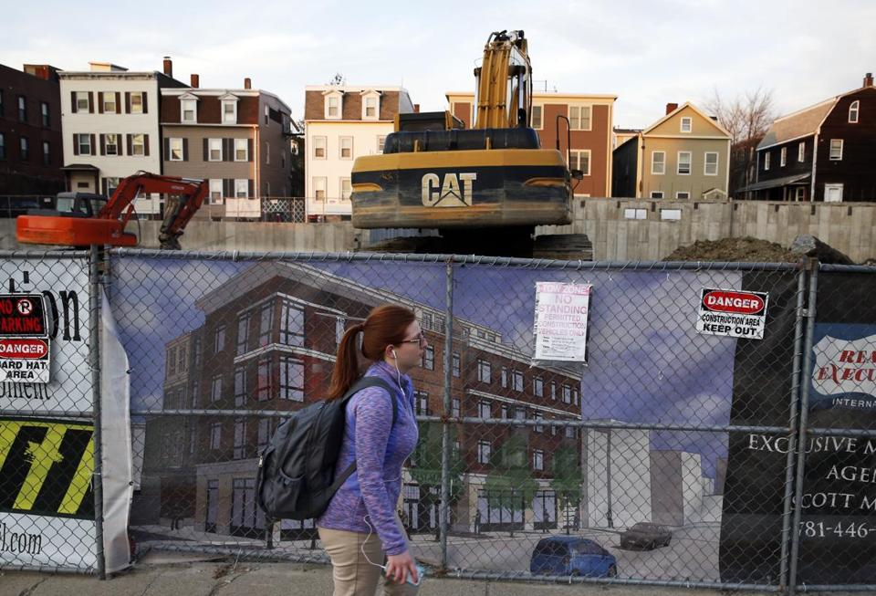 South Boston, MA - 3/9/2016 - A pedestrian walks past new construction in progress on West Broadway along the St. Patrick's Day Parade route in South Boston, MA March 9, 2016. Jessica Rinaldi/Globe Staff Topic: 17parade Reporter: