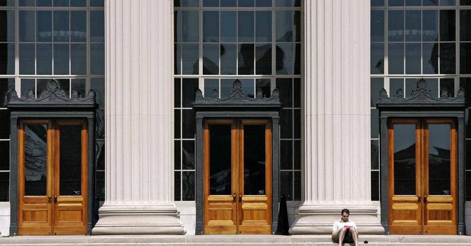 FILE - In this April 22, 2007 file photo, a doctoral student at the Massachusetts Institute of Technology reads outside a building at the Cambridge, Mass. campus. MIT is announcing a pilot graduate program and students will take the first part entirely through MOOCs (massive open online courses). Under the plan, students will pay a fee to get course credit, basically taking classes for a fraction of an MIT tuition. (AP Photo/Michael Dwyer, File)