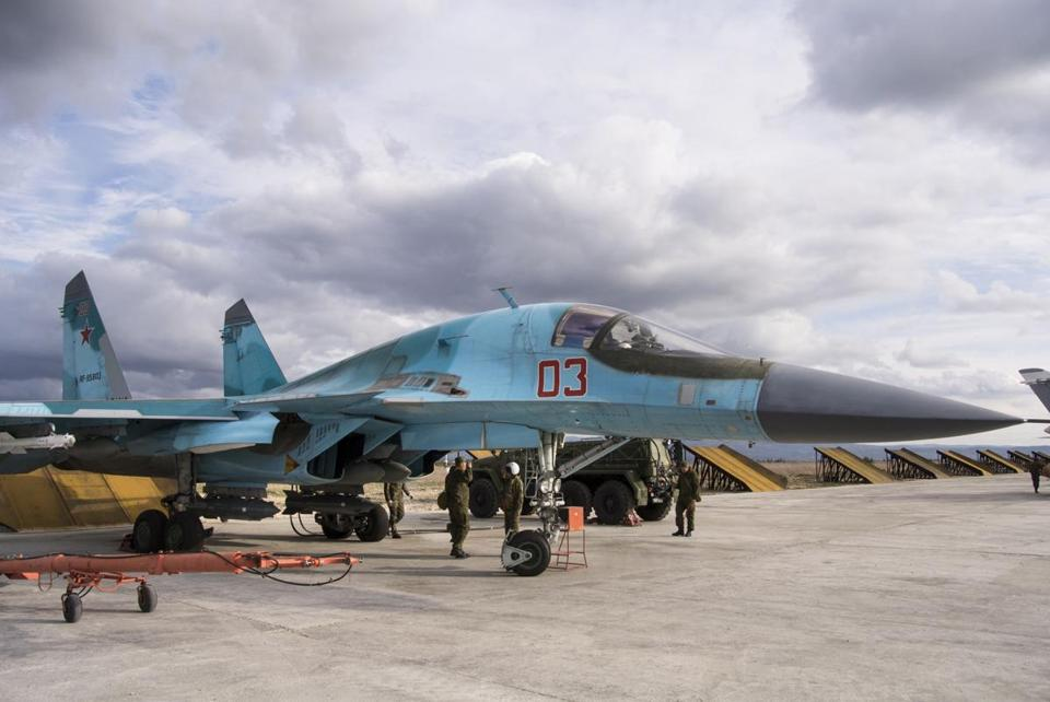 A Russian air force technician reports to a pilot that a Su-34 bomber is ready for a combat mission at Hemeimeem air base in Syria.