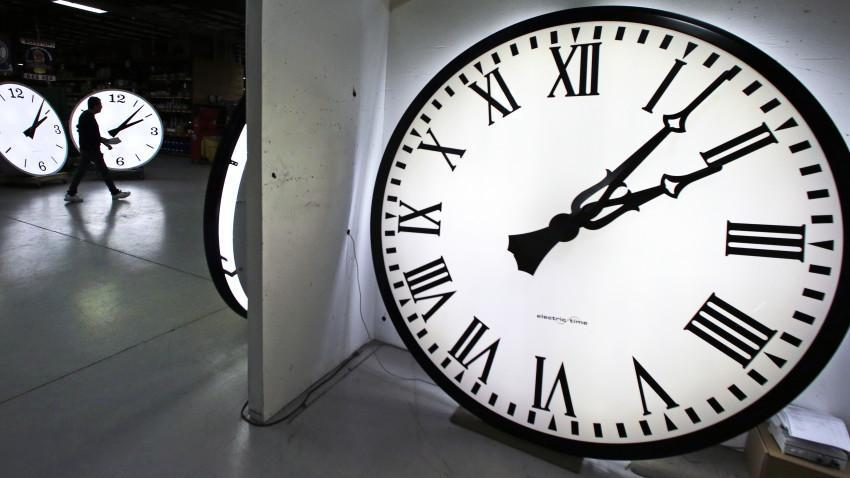 Tom Liberatore, a materials purchasing manager, walks past clocks being tested prior to shipping at the Electric Time Company in Medfield, Mass., Thursday, March 10, 2016. Most Americans will lose an hour of sleep this weekend, but gain an hour of evening light for months ahead, as Daylight Saving Time returns this weekend. The time change officially starts Sunday at 2 a.m. local time. (AP Photo/Charles Krupa)