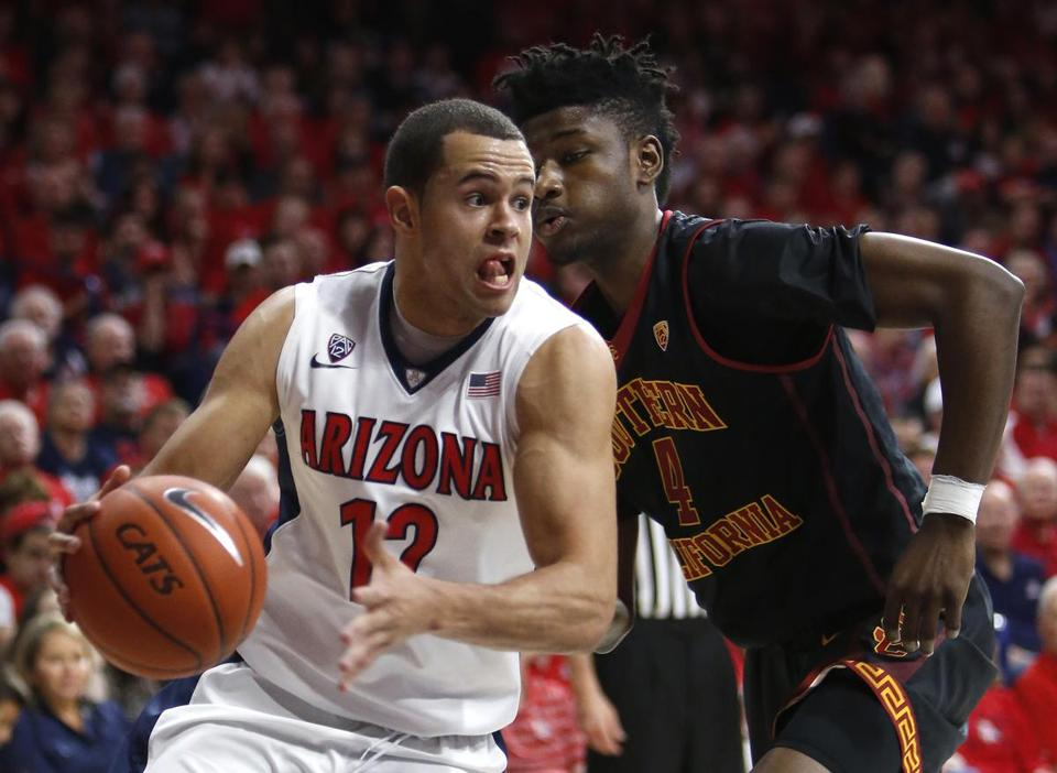 Arizona forward Ryan Anderson (12) drives on Southern California forward Chimezie Metu during the second half of an NCAA college basketball game, Sunday, Feb. 14, 2016, in Tucson, Ariz. Arizona defeated Southern California 86-80. (AP Photo/Rick Scuteri)