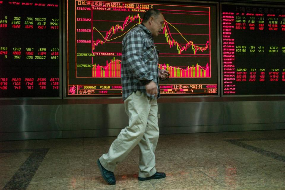 An investor walked past screens displaying stock prices at a securities company in Beijing on Tuesday.