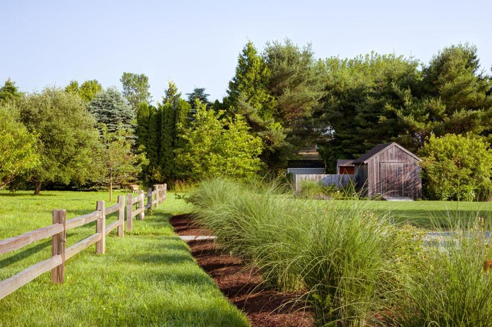 A mixed border of grasses, shrubs, and perennials runs between the pea-stone gravel driveway and the orchard, which sits just beyond the new post-and-rail fence.