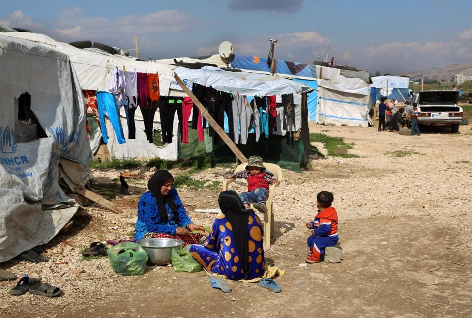Syrian women prepare food for their family outside their tents, at a Syrian refugee camp in the town of Bar Elias, in Lebanon's Bekaa Valley, Tuesday, March 29, 2016. Lebanon is home to more than 1 million registered Syrian refugees, or nearly a quarter of the country's 4.5 million people. Lebanon says that another half a million Syrians live in the country as well and officials say their presence has generated a severe burden that Lebanon is no longer able to face alone. (AP Photo/Bilal Hussein)