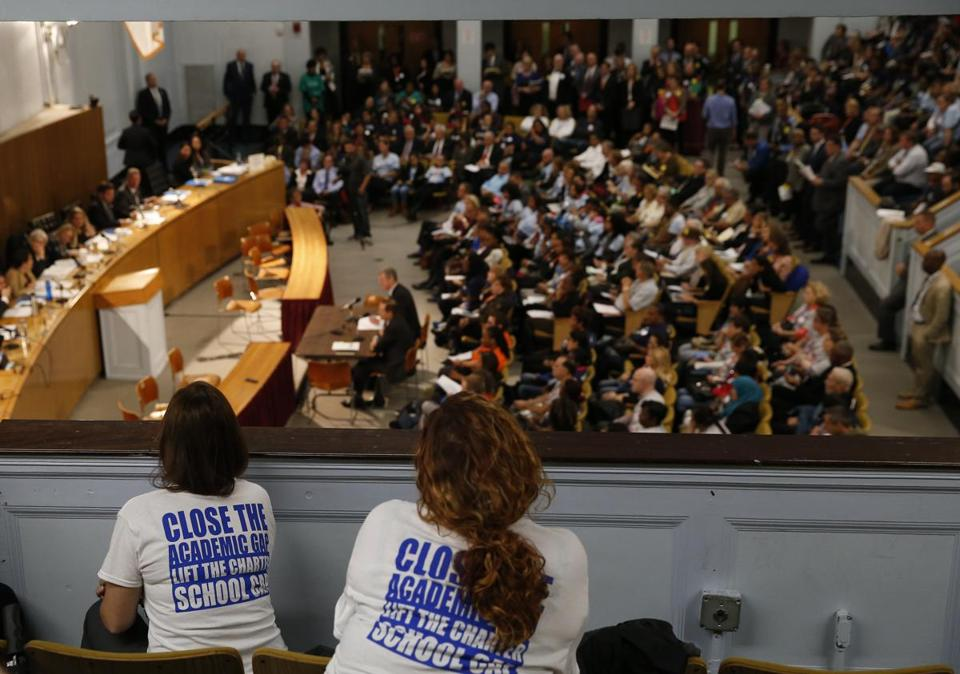 "Women wearing t-shirts that read, ""Close the academic gap. Lift the Charter School cap."" lean over a balcony at the State House Thursday."
