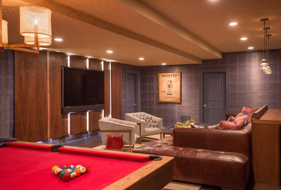 The family basement redesign features a layered feeling with different textures and spaces such as a TV area and a bar.