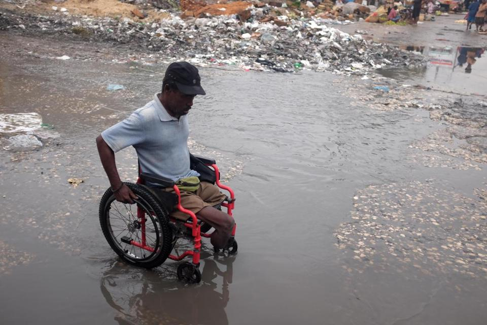 In this Feb. 28, 2016 photo, a wheelchair bound man crosses a street flooded with dirty water in downtown of Port-au-Prince, Haiti. Cholera showed up in Haiti 10 months after a devastating earthquake in the south of the country, deepening the country's misery at a time when it was ill-equipped to cope with the second crisis. (AP Photo/Dieu Nalio Chery)