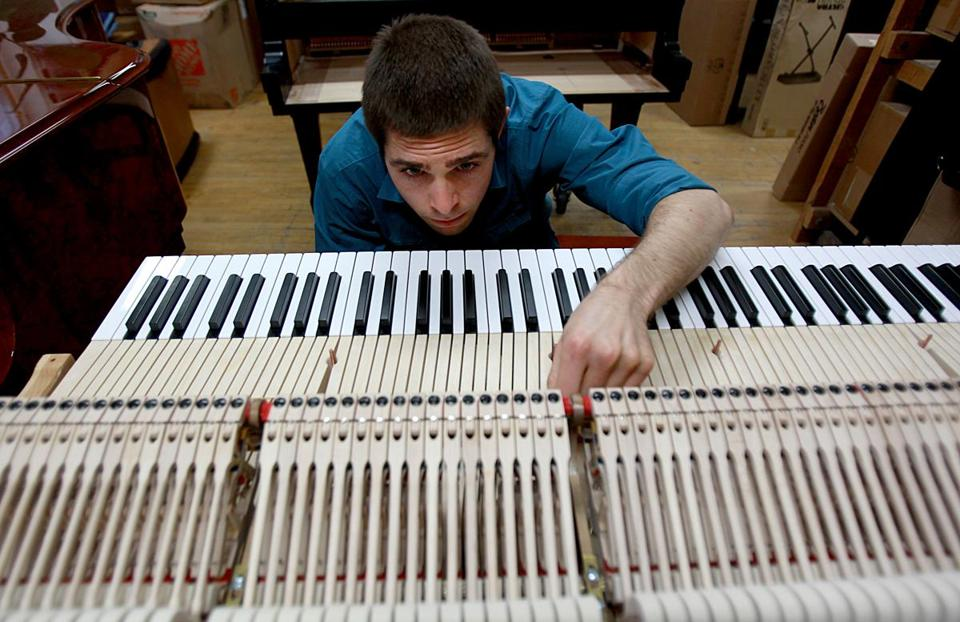 William Grueb, a piano technician, worked on a Steinway piano at M. Steinert & Sons.