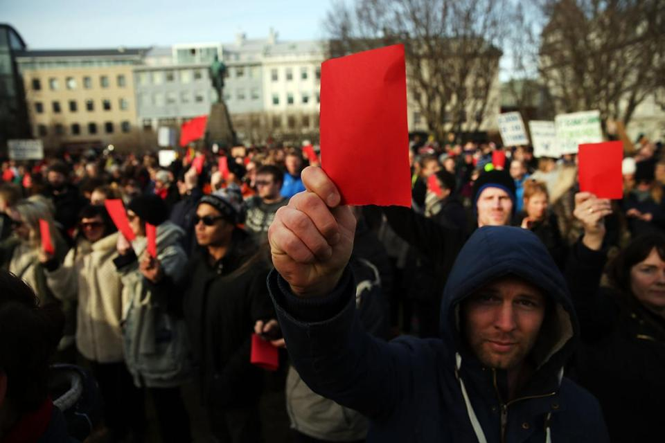 REYKJAVIK, ICELAND - APRIL 07: Hundreds of protesters gather in front of the Parliament building holding red cards for a fourth day on April 7, 2016 in Reykjavik, Iceland. Icelandic Prime Minister Sigmundur David Gunnlaugsson has stepped down after news broke last Sunday that he had hid his assets in an offshore shell-company whose existence was revealed by the Panama Papers. Numerous leaders around the world as well as wealthy individuals have been caught-up in the developing scandal. The island nation of just 320,000 people had only recently recovered from the global banking collapse in 2008. (Photo by Spencer Platt/Getty Images)