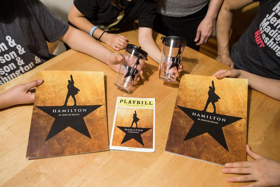 "04/07/2016 BROOKLINE L-R Suk/Stein family members hold Hamilton memorabilia at their home in Brookline. The family loves the Broadway show ""Hamilton"" and owns several T-shirts, cups, playbills and headbands. (Aram Boghosian for The Boston Globe)"