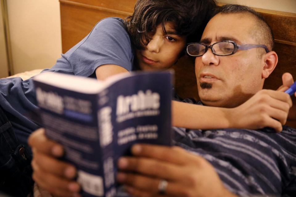 Ahmed Al Rubaye (right) and his son, Abdul Wahab, 11, study an Arabic to English dictionary in their room at the Colonial Traveler Inn in Saugus.