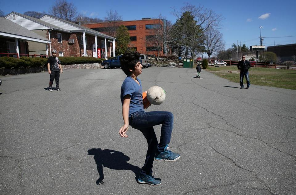 Abdul Wahab Al Rubaye plays soccer with his family outside their room at the Colonial Traveler Inn in Saugus.