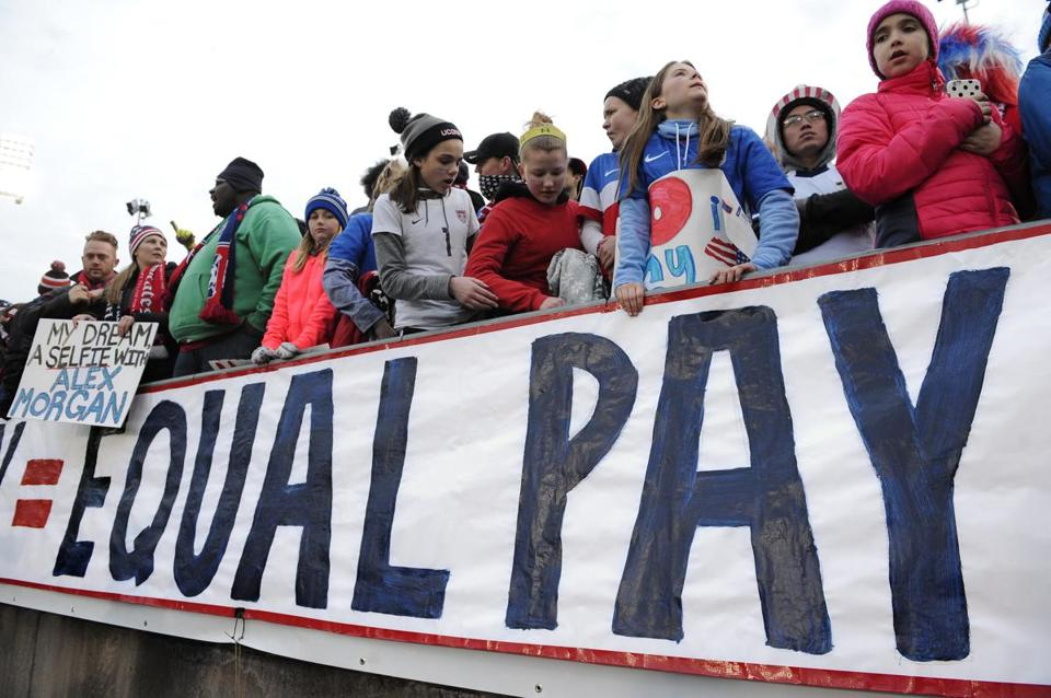 Fans stand behind a large sign for equal pay for the women's soccer team during an international friendly soccer match between the United States and Colombia at Pratt & Whitney Stadium at Rentschler Field in Connecticut in April 2016.