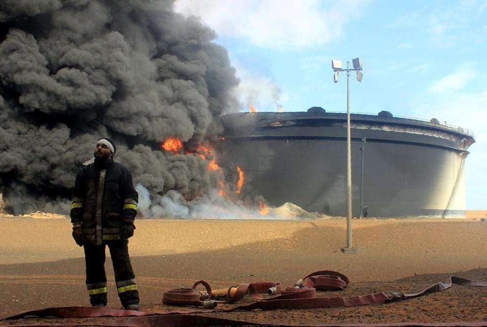 Libyan fireman stands in front of smoke and flames rising from a storage tank at an oil facility in northern Libya's Ras Lanouf region on Jan. 23. The tank was set ablaze earlier in the week following attacks launched by Islamic State group jihadists to seize key port terminals.