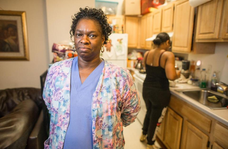 Sharon Brown, shown in her Dorchester apartment after arriving home from her second job, works in a nursing home during the day and in an assisted living facility at night to make ends meet.