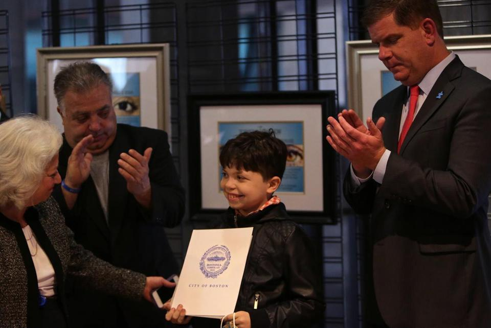 Boston, MA - 04/12/16 - Karen DiLoreto, cq, Executive Assistant to Suffolk County District Attorney Daniel Conley, congratulates award recipient Borias Lake, cq, 13, as his dad William and Mayor Marty Walsh look on during today's Now You See Bravery Awards ceremony at Boston City Hall. The awards recognize children and adult survivors of abuse, neglect, and exploitation who had the courage to disclose those offenses and take part in the prosecution of their abusers. - (Barry Chin/Globe Staff), Section: Metro, Reporter: Travis Anderson, Topic: 13bravery, LOID: 8.2.2602477193.