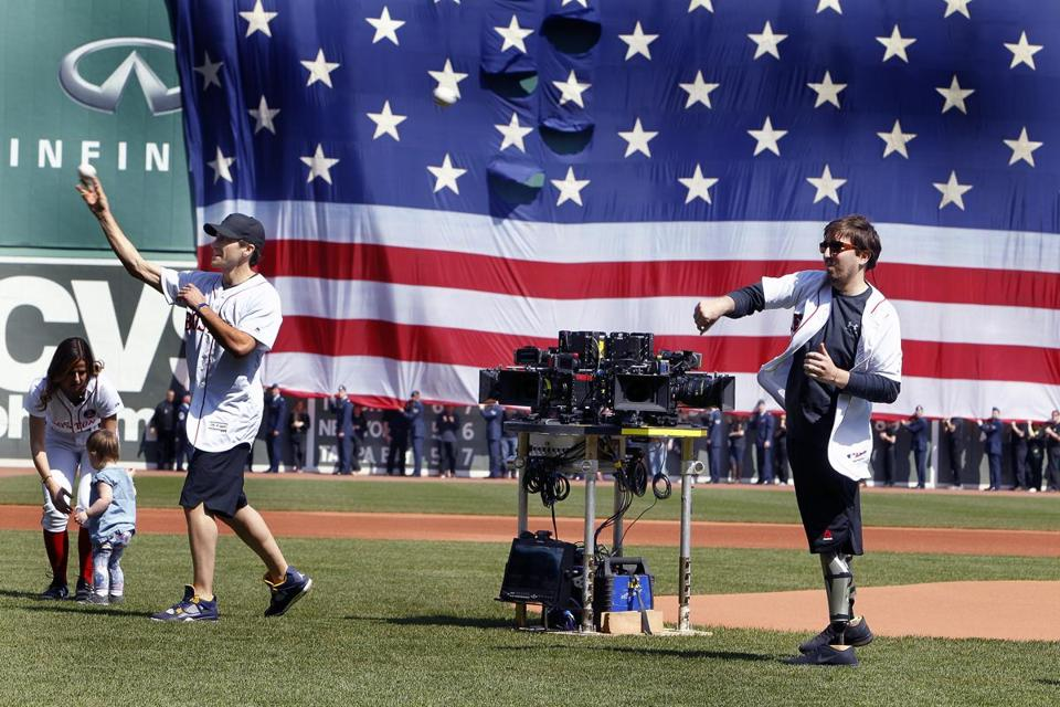 Boston Marathon bombing survivor Jeff Bauman (right) and Jake Gyllenhaal (left) were pictured as they threw out the first pitch.