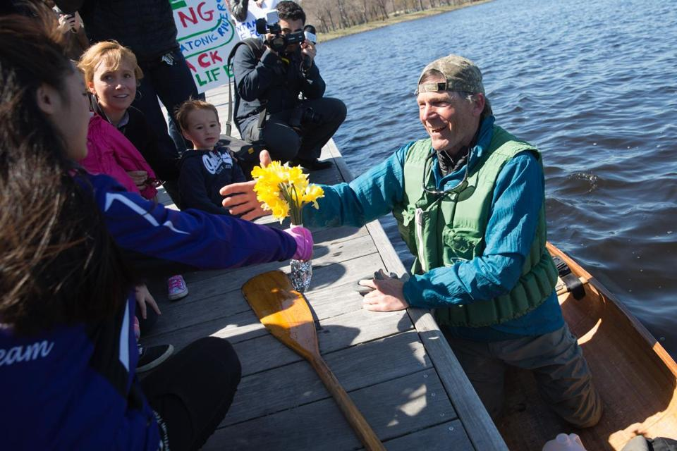 Boston, MA - 4/20/2016 - Denny Alsop receives flowers from third graders from Muddy Brook Elementary school as he comes ashore on the Charles River Esplanade after completing a one month canoe trip across the waters of the commonwealth in an effort to highlight needed cleanup of the Housatonic River in Boston, MA, April 20, 2016. (Keith Bedford/Globe Staff)