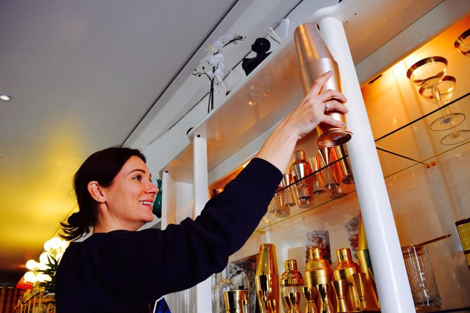 Kristen Voisey of the BYOB Cocktail Emporium shows a shaker to a customer.