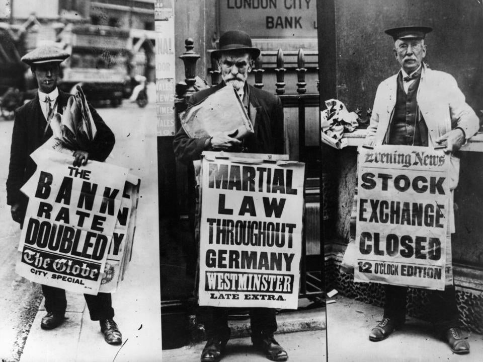 1st August 1914: Three street news vendors displaying their headline boards relating to the financial crisis and martial law in Germany. (Photo by Hulton Archive/Getty Images)