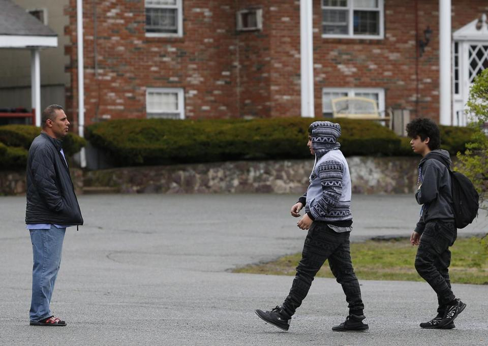 Ahmed al Rubaye met his children as they got off the bus in Saugus on Tuesday. The state had threatened to evict them from their motel for allowing guests inside their rooms.