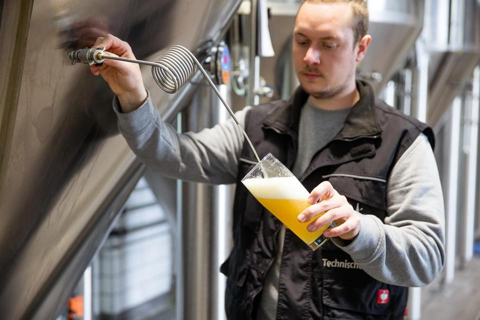Braumeister Simon Rossmann draws a beer at Giesinger Brau, which started in a garage and is now Munich's largest craft brewer.
