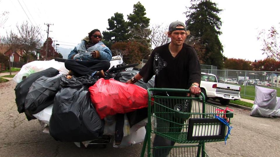 "Jason Witt, accompanied by Heather Holloman, hauls a cart of recyclables in ""Dogtown Redemption."""