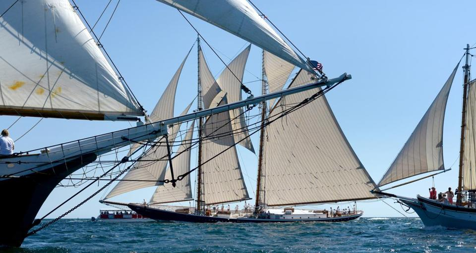 Gloucester, MA: 09-06-2015: The schooner Columbia (center) is framed by bowsprits while sailing off Gloucester, Mass. in the Mayor's Race during the Gloucester Schooner Festival Sept. 6, 2015. The Columbia is a steel hulled replica of the original Gloucester fishing schooner Columbia, launched in 1923. (Waiting official race results to confirm that Columbia won.) Photo: John Blanding, Boston Globe staff (feature) (Photo taken for personal project, fine for Boston Globe to use, no further distribution please.)
