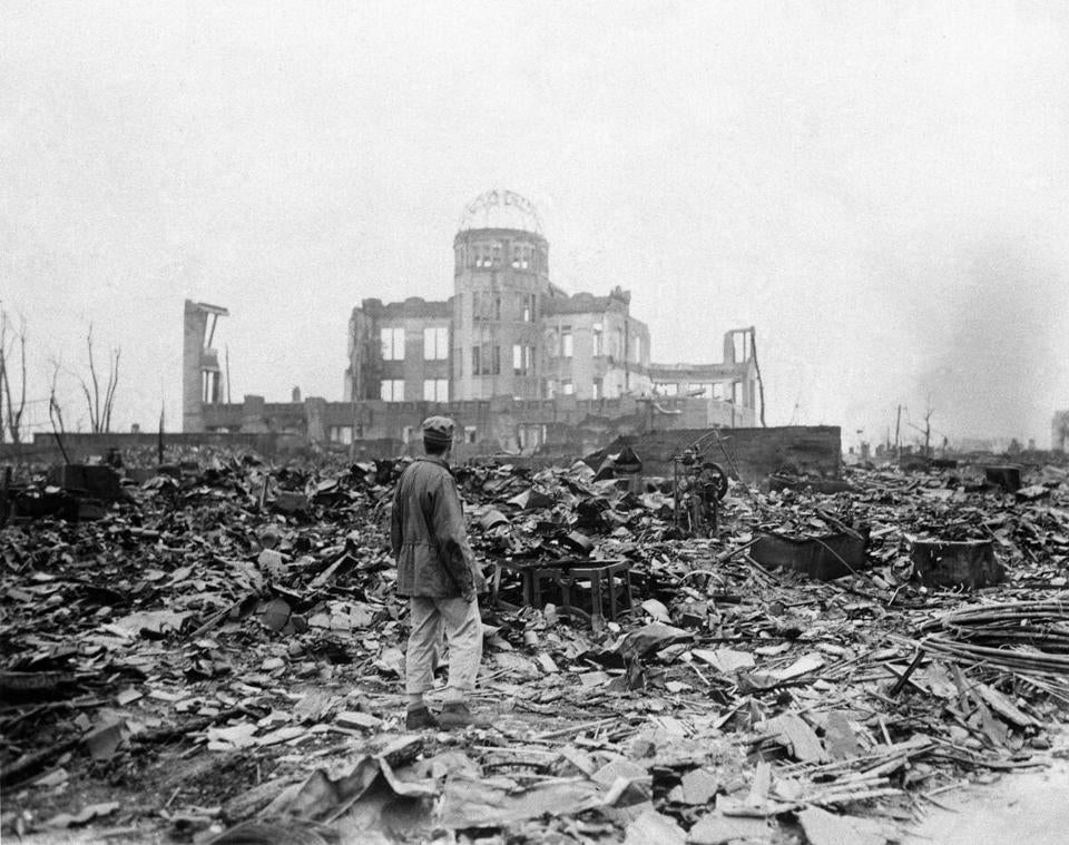 FILE - In this Sept. 8, 1945 file photo, an allied correspondent stands in the rubble in front of the shell of a building that once was a movie theater in Hiroshima, Japan, a month after the first atomic bomb ever used in warfare was dropped by the U.S. on Monday, Aug. 6, 1945. In a moment seven decades in the making, President Barack Obama this month will become the first sitting American president to visit Hiroshima, where the U.S. dropped an atomic bomb during World War II, decimating a city and exploding the world into the Atomic Age. (AP Photo/Stanley Troutman, File)